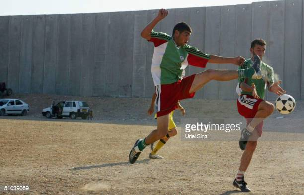 Palestinian boy's play soccer alongside Israel's separation barrier on July 9 2004 where the 9meterhigh concrete wall cuts the West Bank Palestinian...