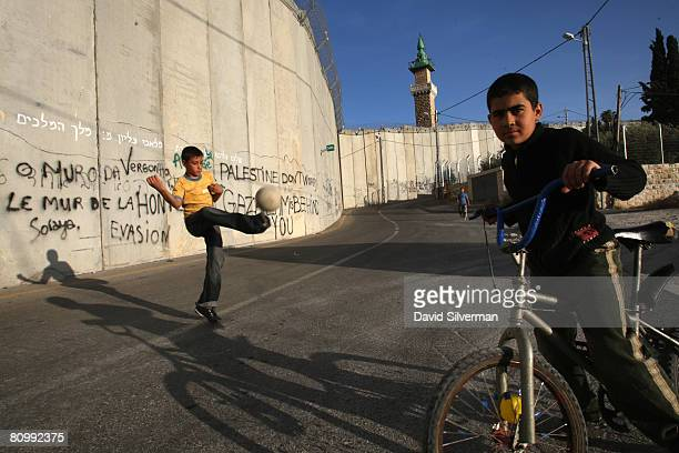 Palestinian boys play under Israel's separation barrier May 4 2008 where the controversial 30foothigh wall cuts Bethany Abu Dis and other West Bank...