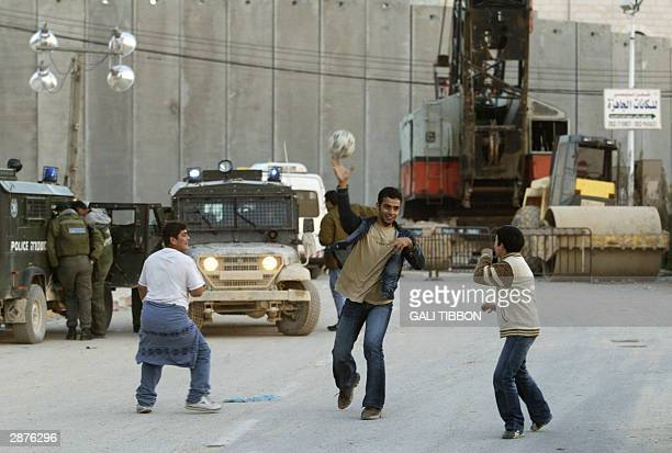 Palestinian boys play with a ball in front of Israel's controversial 'security' wall in Abu Dis separating it from Jerusalem 17 January 2004 Israeli...