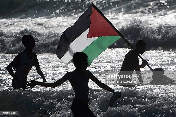 Palestinian boys play with their national flag on a beach near the former Israeli settlement of Neve Dekalim 12 September 2005 Thousands of residents...