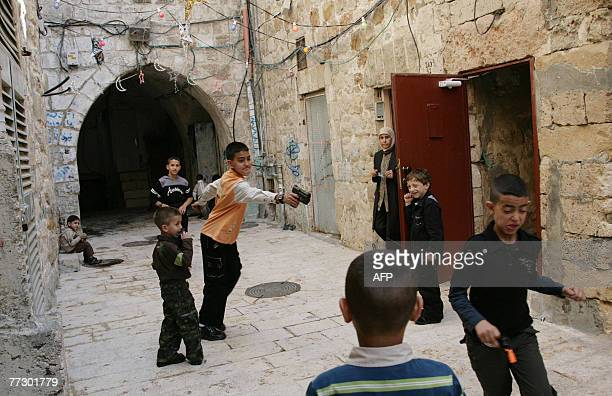 Palestinian boys play with their new plastic toy handguns on the first day of Eid alFitr marking the end of the holy month of Ramadan in Jerusalems...