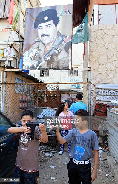 Palestinian boys play with their toy guns under a poster of executed Iraqi president Saddam Hussein in the refugee camp of Shatila in the southern...