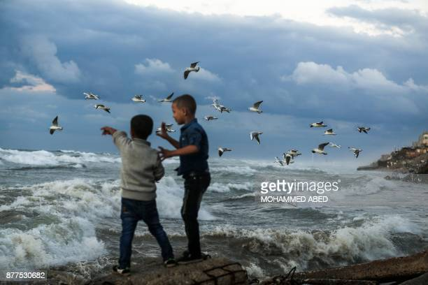 Palestinian boys point at birds flying by the roaring waves at the beach in Gaza City on November 22 2017 / AFP PHOTO / MOHAMMED ABED