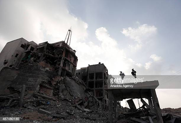 Palestinian boys practice parkour skills amid the ruins of buildings which were destroyed by Israeli offensives in Beit Lahia town of Gaza on October...