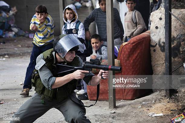 Palestinian boys react in the background as an Israeli police officer aims his weapon during clashes with Palestinian youths following an arrest...