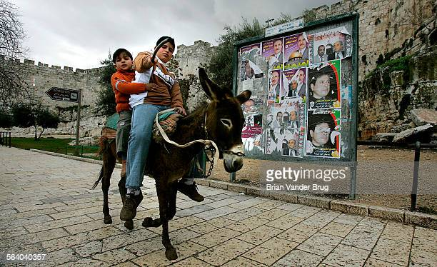 Palestinian boys ride a donkey past election posters on a signboard near the Damascus Gate outside the walled Old City in East Jerusalem Friday...