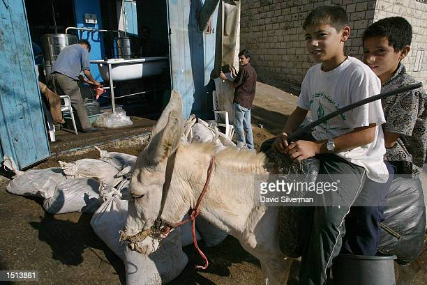 Palestinian boys ride their donkey past the regional olives press in Akraba October 21 2002 near Yanun West Bank Israeli soldiers were deployed to...