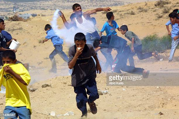 Palestinian boys run from teargas canisters thrown by Israeli soldiers as a youth throws it back towards Israeli soldiers during clashes September 28...