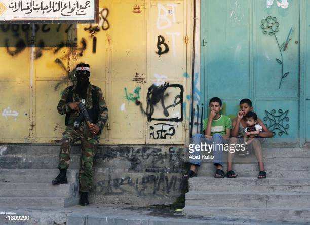 Palestinian boys sit next to a militant while he guards the streets for a possible Israeli army ground operation at the Jabalia refugee camp on June...