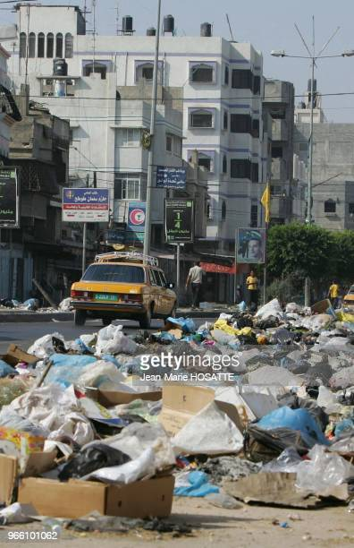 Palestinian boys stand next to garbage on a street August 26 2007 in Gaza City Gaza Municipal workers have been on strike for nine days due to a lack...