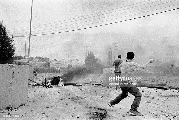 CONTENT] Palestinian boys throw stones against israeli soldiers during a demonstration during Second Intifada nearby a next a jewish settlement near...