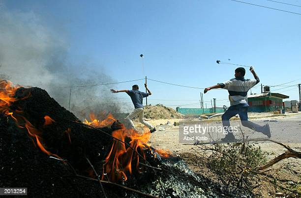 Palestinian boys throw stones at an Israeli tank during a clash May 19 2003 at Beit Hanoun town in the northern Gaza Strip Israeli troops continued...