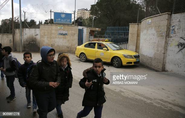Palestinian boys walk past a United Nations' run school in the Qalandia refugee camp near Ramallah in the West Bank on January 17 2018 after the...