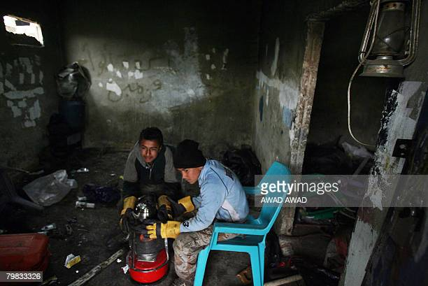 Palestinian boys warm up next to a kerosine heater at a mechanics workshop in the Baqaa refugee camp near the Jordanian capital Amman on February 19...