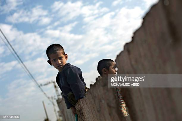 Palestinian boys watch as Islamist movement Hamas policmen jog along the streets in Gaza City on November 12 three days before the first anniversary...