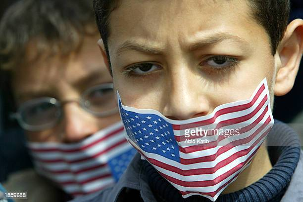 Palestinian boys wear American flag stickers over their mouths during an antiUS rally March 20 2003 in Rafah refugee camp in the Gaza Strip Tomahawk...