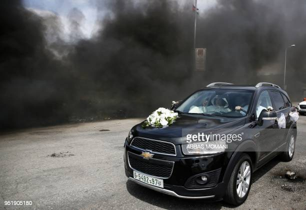 Palestinian bride sits in a car as smoke billows from tyres in flame during clashes between Palestinians demonstrators and Israeli troops near the...