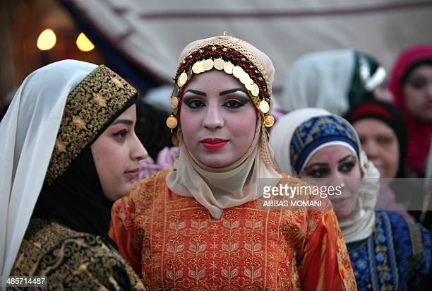 Palestinian brides stand during a mass wedding ceremony in the West bank city of Jericho on Januray 28 2014 Nearly 300 Palestinians were married in...