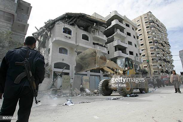 Palestinian bulldozer cleans the streets after an Israeli airstrike on a building belonging to the Hamas Government's interior Ministry which...