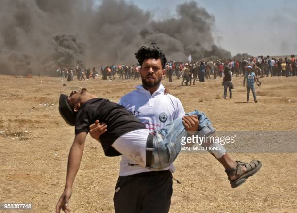 Palestinian carries an injured protester during clashes with Israeli forces near the border between the Gaza strip and Israel east of Gaza City on...