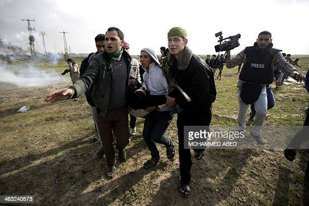 Palestinian carry a fellow protester wounded during clashes with Israeli forces near the Nahal Oz border crossing with Israel east of Gaza City on...