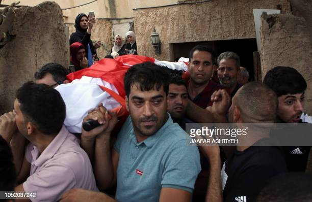 Palestinian carry the body of 48yearold mother of eight Aisha Rabi who died of her wounds after the car she was travelling in with her husband was...