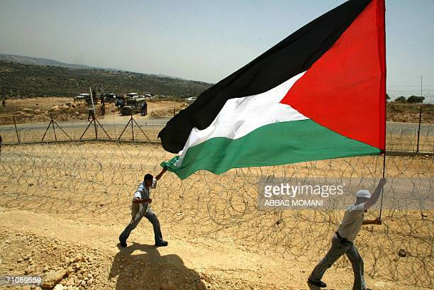 Palestinian carry their national flag next to the path of the Israeli separation barrier in the West Bank village of Bilin 26 May 2006 Palestinian...