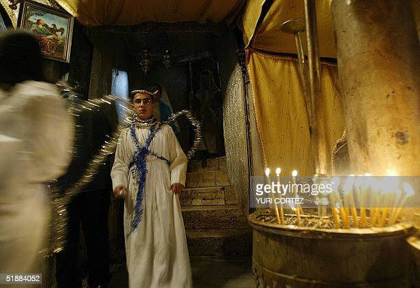 Palestinian Catholic children dressed likes angels visit the grotto of the Church of the Nativity in the West Bank town of Bethlehem 21 December 2004...
