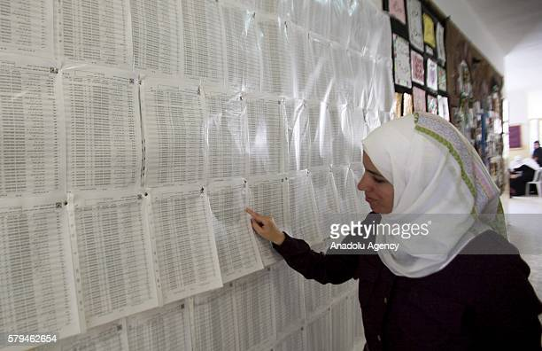 Palestinian checks her name on the polling list at a polling station prior to upcoming local elections which will be held in October 2016 in Nablus...