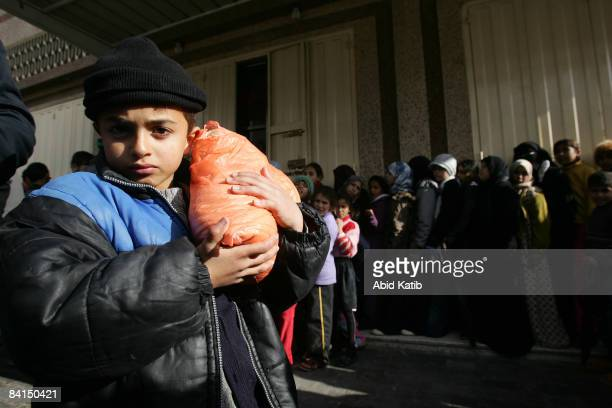 Palestinian child carries a bag of bread while other Palestinians queue up to buy bread outside a bakery on December 31, 2008 in the Jabalia refugee...