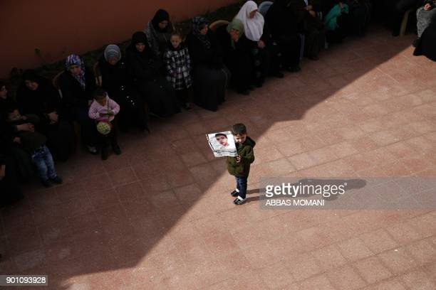 Palestinian child carries a poster of Musab Firas alTamimi who was shot dead in clashes with the Israeli army a day earlier during his funeral in the...