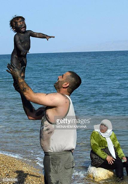 A Palestinian child covered with the Dead Sea mud is lifted up by his father as they enjoy the Muslim feast of Eid alFitr at the Ein Gedi resort on...