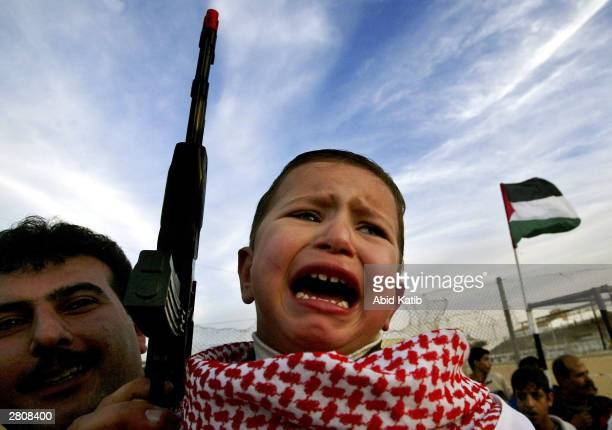 Palestinian child cries as he holds a toy gun during a demonstration held to mark the 36th anniversary of the creation of the Popular Front for the...