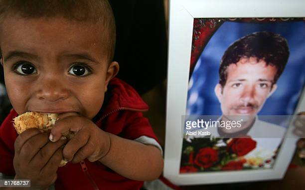 Palestinian child eats bread as he sits next to his father's photo during a protest calling for the release of Palestinian and Arab prisoners from...