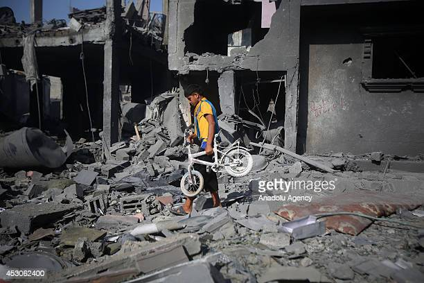 Palestinian child finds his bicycle on the rubble after the attack of Israel in Rafah Gaza on 2 August 2014