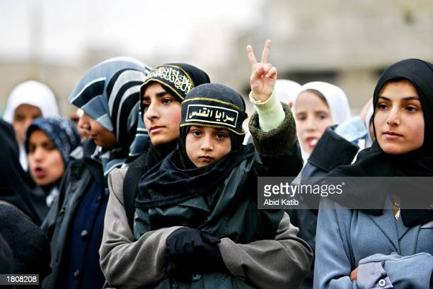 Palestinian child flashes Vsign as she carried by her sister while attending a rally for the militant Islamic Jihad group February 21 2003 in Gaza...