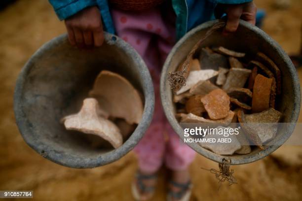 A Palestinian child holds buckets full of pottery fragments at a freshlydiscovered cemetery in the garden of a house in Beit Hanun in the northern...