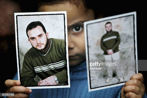 Palestinian child holds the photos of her father who is a prisoner jailed in Israel as she attends a protest at the headquarters of the International...