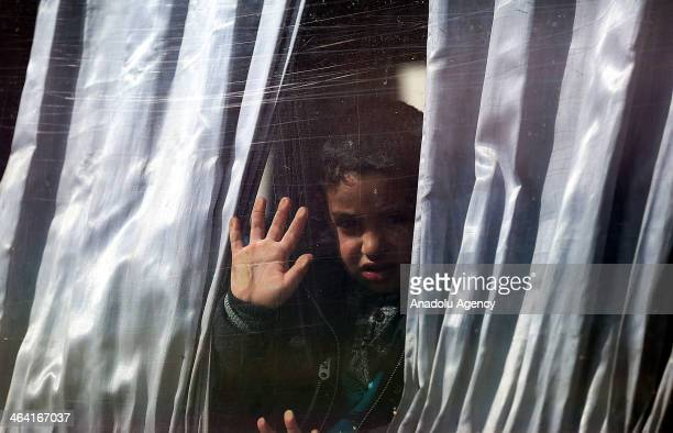 Palestinian child hoping to cross into Egypt look out a bus window at the Rafah crossing between Egypt and the southern Gaza Strip on January 21 2014...