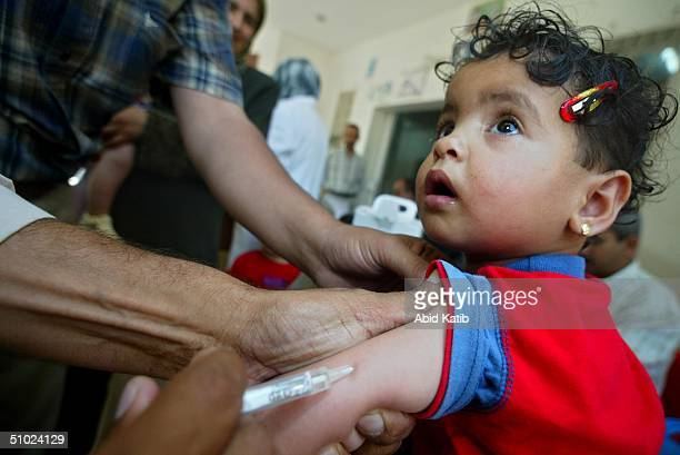 Palestinian child is vaccinated against measles and vitamin A deficiency at Al-Shouhda Rafah health center during the national campain for protection...