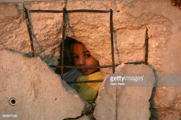 Palestinian child looks through a wall damaged by a rocket during the intifada on the Egyptian side of the now EgyptianPalestinian controlled border...
