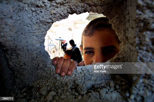 Palestinian child peers through a hole in the wall as other Palestinians inspect the rubble of their destroyed homes January 13, 2004 in Rafah...
