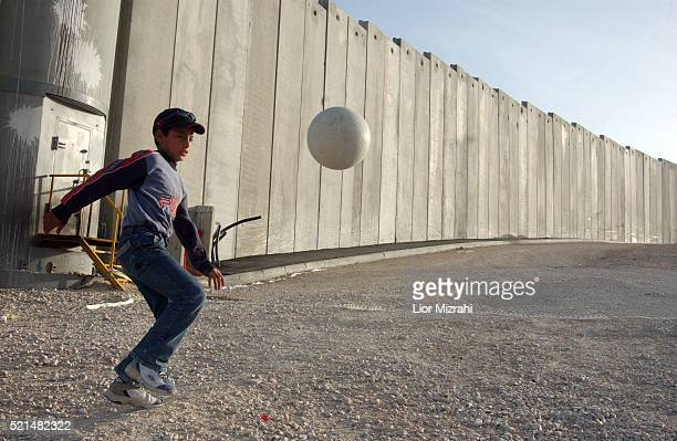 Palestinian child plays by the separation wall in the village of A-tur located on the outskirts of East Jerusalem Tuesday March 01, 2005.