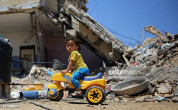 Palestinian child plays in front of the rubble of buildings which were destroyed during the 50day war between Israel and Hamas militants in the...