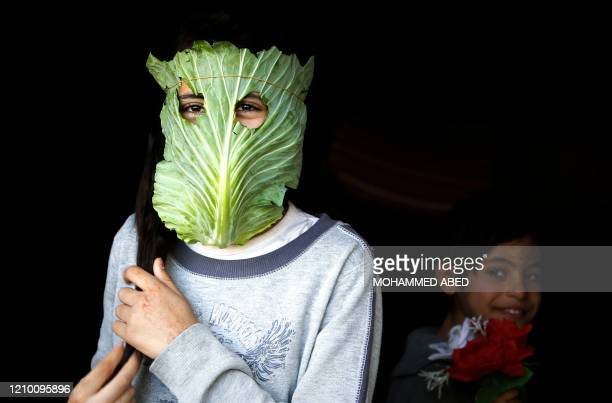 Palestinian child poses with a makeshift mask made of cabbage in Beit Lahia in the northern Gaza Strip on April 16, 2020 amid the coronavirus...