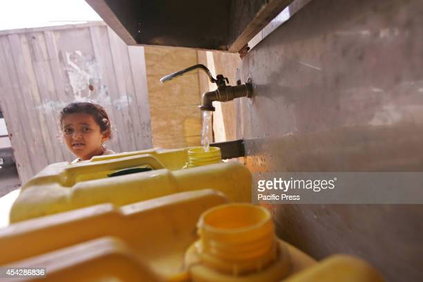 Palestinian child pours water into a container from a desalination plant after the war ended officially in Rafah Southern Gaza strip