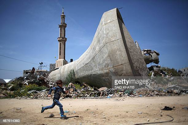 Palestinian child runs past a water tank that was destroyed in Israeli bombing during the 50-day war between Israel and Hamas militants in the summer...