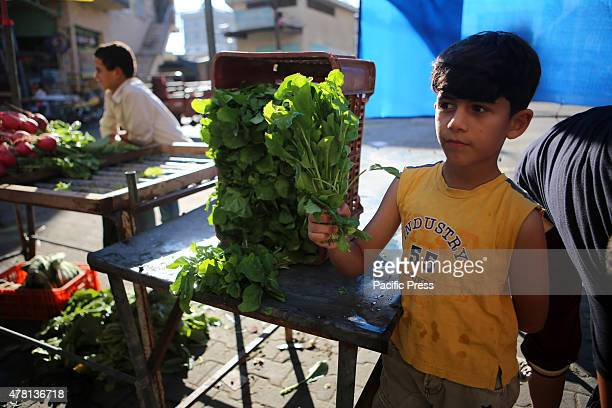 Palestinian child selling the watercress in a street market on the fifth day of the holy month of Ramadan in Rafah in the southern Gaza Strip