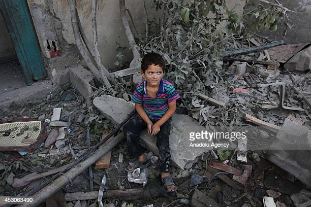 Palestinian child sit on the rubble of Imam Shafi'i Mosque destroyed in Israeli airstrikes in the Zeitoun neighborhood of Gaza City on August 02 2014