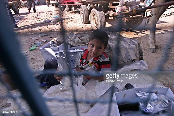 Palestinian child sits between sacks of aid from the UNRWA after the war ended officially in Rafah Southern Gaza strip
